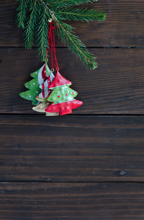 Christmas toys fir tree hanging over wooden background photo