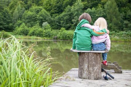 두 개의 작은 아이 포옹 서로와 호수 전망을 보면 스톡 콘텐츠
