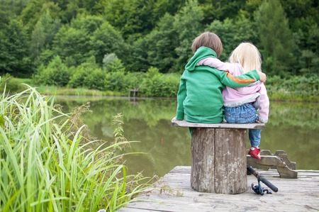 banc de parc: Deux petit câlin de l'enfant de l'autre et de regarder une vue du lac Banque d'images