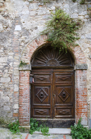 Wooden door in old stone house, , Italy photo