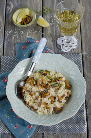 Risotto with chanterelles and parmasan on wooden table photo
