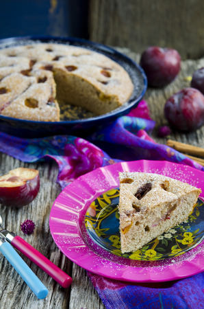 Plum cake with cinnamon on wooden table photo