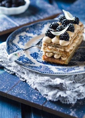 french pastry: Milhojas, pasteler�a franc�s con crema pastelera y blackberry en un plato azul y mesa de madera