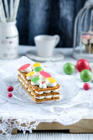 french pastry: Millefeuille, french pastry with custard and chocolate on a white plate and wooden table Foto de archivo