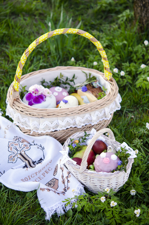 paskha: Easter. Easter basket with painted eggs and Easter cake on the spring green grass