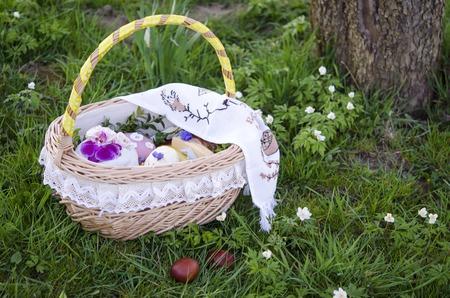 religion catolica: Pascua de Resurrección. Cesta de Pascua con huevos pintados y torta de Pascua en la hierba verde de la primavera Foto de archivo