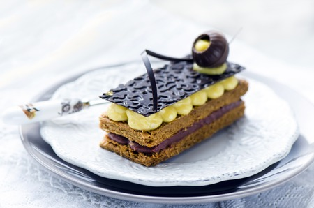 pasteleria francesa: Milhojas, pastelería francés con crema pastelera y chocolate en un plato blanco y mesa de madera