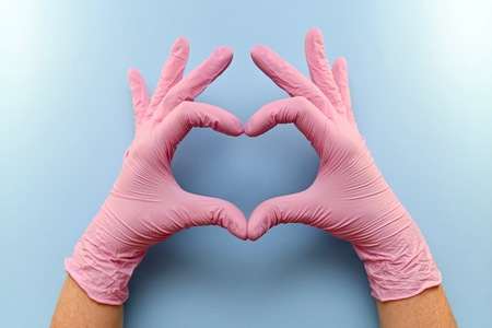 The heart, figure built from the hands in pink rubber medical gloves on a blue background. Archivio Fotografico