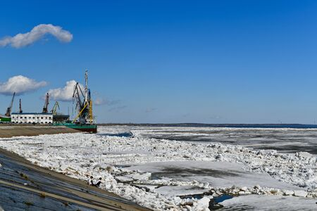 SURGUT, KHANTY - MANSIYSKIY AVTONOMNYY OKRUG, ROSSIYA - MAY 5, 2019:  Port part of the Ob Quay. Ice drift. The boys approach the river, they are attracted by the cold blocks of ice. 報道画像