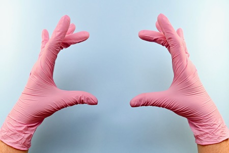 Two palms of hands in pink rubber medical gloves. On something like hold, or show the size of something. Fingers spread out. On a blue background.