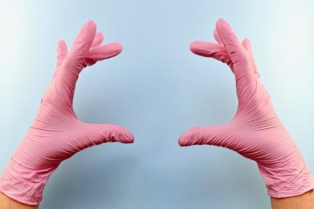 Zwei Handflächen in rosa medizinischen Gummihandschuhen. Auf etwas wie halten oder die Größe von etwas anzeigen. Finger gespreizt. Auf blauem Hintergrund.
