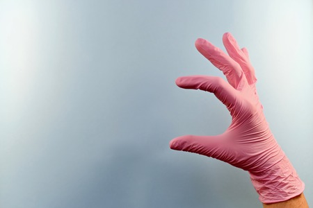 A hand in a pink rubber medical glove holding a silt shows. On a blue background, on the right.