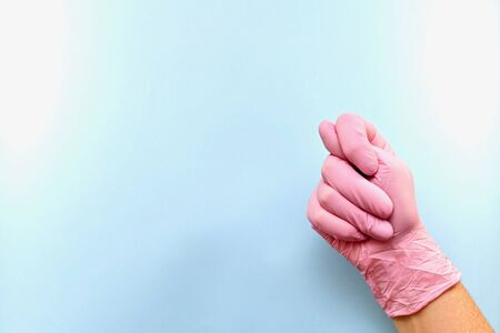 ight hand, clenched into a fist, and folded into a gesture with a bulging thumb, between the index and middle, inside. Wearing pink medical rubber gloves on a blue background, right, diagonal. 스톡 콘텐츠