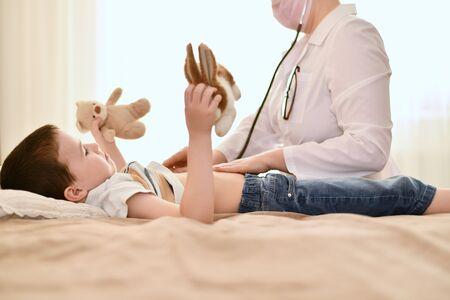 Un bambino con giocattoli di peluche in entrambe le mani giace sul letto e guarda dispiaciuto il dottore che è venuto da lui.