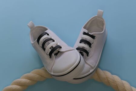 White sneakers with silicone laces clasps, with black small details. On a rope rope laid out in an arc. Right pair on the left. On a light blue background.