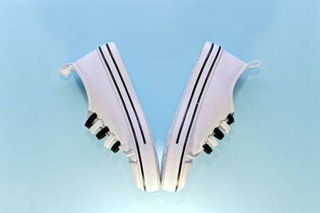 A victory symbol lined with a pair of white sports shoes with silicone laces and black details. Socks together, heels apart. On a blue background.