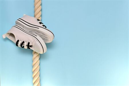A pair of sports shoes, the soles to the soles obliquely on a vertically hanging rope. On the azure background.