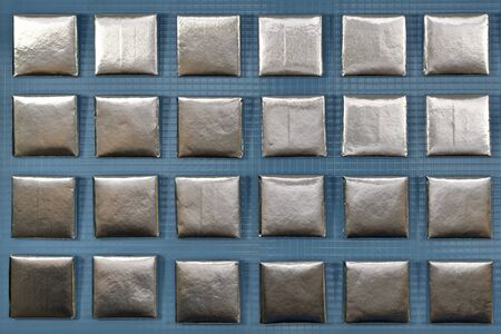 Aluminum chocolate squares in rows on a blue plastic background.