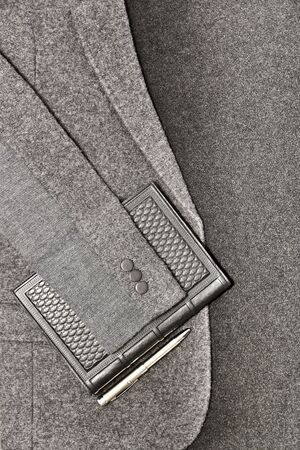 Notebook with pen on a background of a jacket on a gray cloth.
