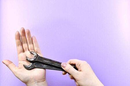 Two women hands, in the brush of one hand two wrench keys, lie on the palm of the other, on a light purple background with free space.