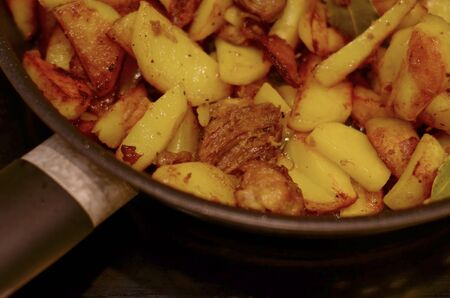 Potatoes with meat cut, toasty, largely removed sideways in a frying pan.