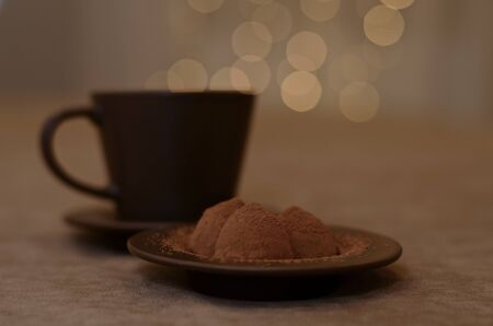 A dark brown coffee cup with a saucer and a plate with three chocolate cone shaped candy pyramids, steaming over the cup in the form of a side, on a velvet smoky background.