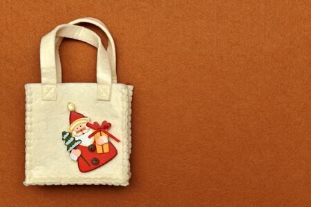 Handbag with handles, with decorative wooden figurine of Santa Claus sewn in the corner, on a red felt background.