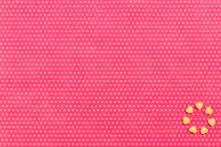 Yellow drazhe hearts laid out in the form of a circle at the bottom right in the corner on a textile background, fuchsia with a print in white polka dots. View from above.