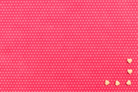 Yellow small hearts are framing a corner on a textile background, fuchsia with a print in white polka dots. View from above.
