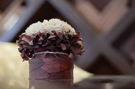 The bouquet is decorated with artificial light roses with burgundy leaves of the container tied with a coarse rope, a light pointer on the background of a wooden rhomboid lattice. 写真素材