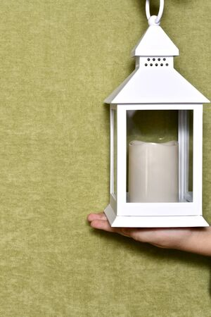 White lantern decorative with a candle inside, in the form of a house with a roof, on the child's palm, against the background of green velvet.