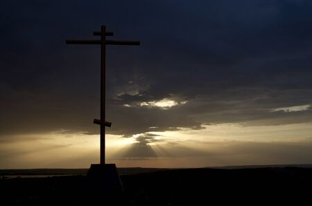 The silhouette of the cross is illuminated from behind by the rays of the sunset against the dark gloomy sky.