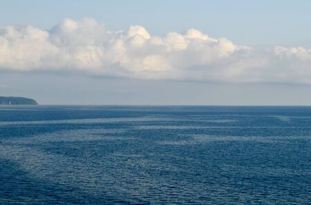 A strip of blue sea and a strip of blue sky. With three barges sailing one by one, and a cloud over them. Banco de Imagens