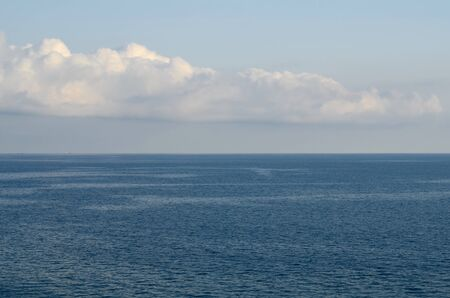Two lanes, sea and sky. Two barges on the horizon and a white cloud hovering in the sky. 版權商用圖片