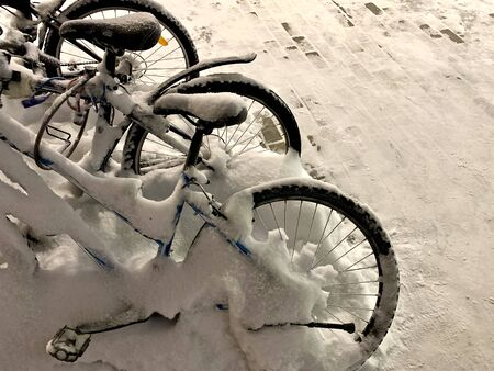 Three uniformly superimposed adult two-wheeled bicycles in the snow outside in winter.