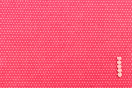 A plush fuchsia background in white polka dots with a decorated on the right in the corner with five vertical hearts.
