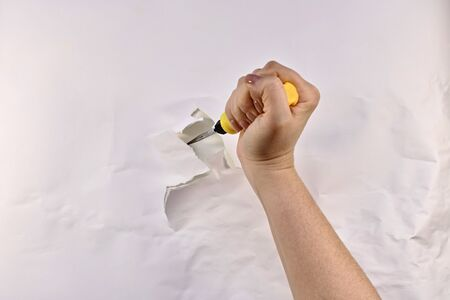 A screwdriver, with a yellow handle, in a tightly compressed woman's hand, stuck in a wall with a white paper ragged hole.