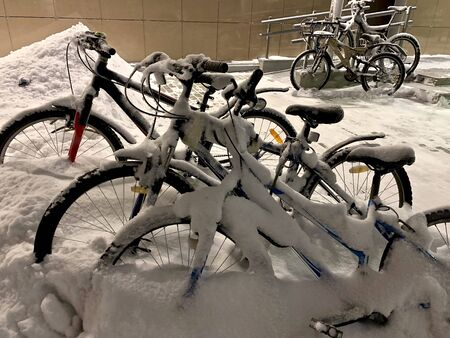 Three snow-covered two-wheeled adult bikes in the foreground and two distances parked to a pole near the buildings home. Stock Photo