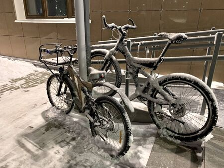 Two snow-covered adults bike, one with a makeshift basket to carry a child or cargo in front, the other with an extravagant unusual steering wheel, high-seated and wide rubber, on the street in winter. Stock Photo