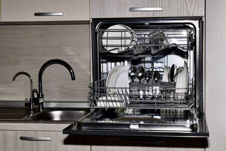 The dishwasher with an open square panel is conveniently located next to the sink and at its level, with clean dishes in bright colors, shot in front with lights on the cutlery.