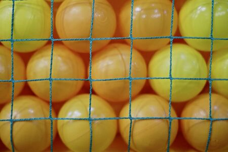 The balls are yellow plastic in large quantities in closeness behind the green mesh in the form of a background.