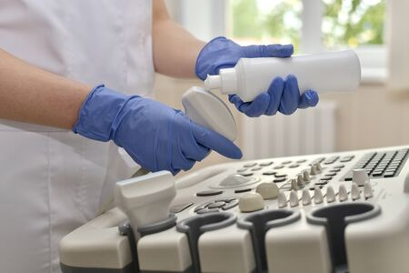 A doctor in blue gloves, with an outstretched index finger begins to apply a transparent gel to the ultrasound scanner sensor above the control panel.