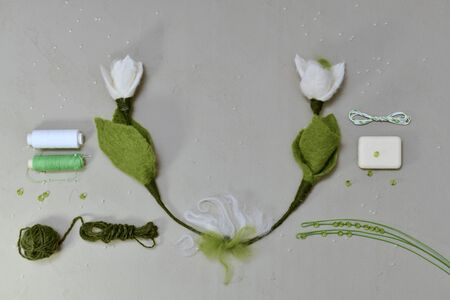 Ready snowdrops made of wool in a semicircle in the center and at the edges of the tool and materials for work.