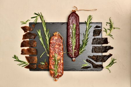 Raw smoked beaver and roe deer sausages jerky wild with sprigs of rosemary flat lei on a black slate substrate on gray plaster.