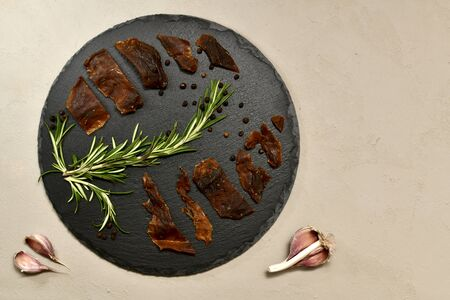 Spread wild rabbit jerky on a black slate circle with spices and garlic on a gray stucco on the left.