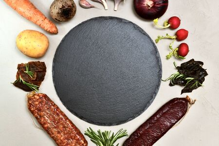 A slate round substrate in the center on a gray plaster background and a frame with groceries around, large shot snippet.