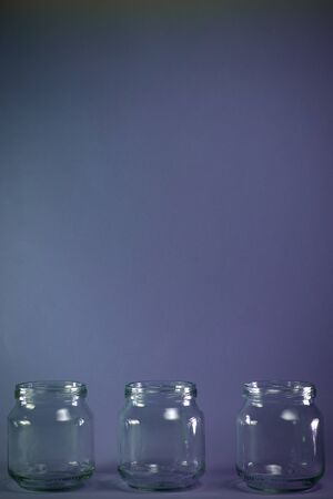 Three glass jars lined in a horizontal row at the bottom of the frame, with a free magenta-colored background space at the top.