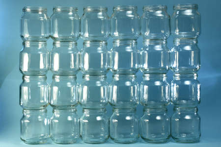The background, four floors wall, even horizontal rows, is from the built wall of transparent small cans. Stock Photo