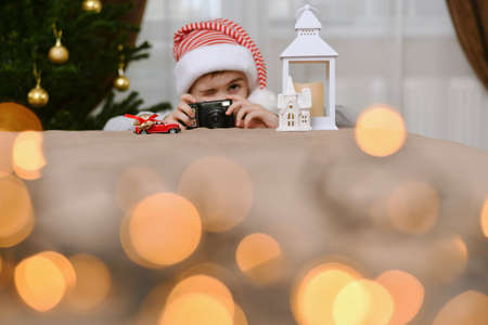 A child with no mirror automatic camera, took aim, squinting one eye, photographing a car with Christmas gifts.