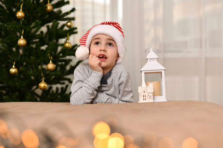 Little boy making a wish. He put his hand under his head. Dressed in a red and white striped carnival cap. Sits in a festively decorated room near the tree. Stock fotó